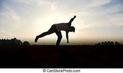Parkour tricker jumper performs amazing flips, silhouette...