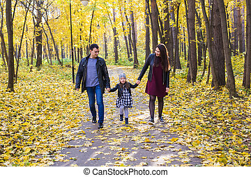 Parks, nature and family concept - Happy family walking in autumn park