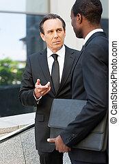 parlare, circa, business., due, fiducioso, uomini affari, parlare, e, gesturing, mentre, standing, fuori