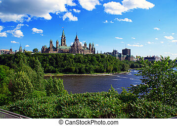 Canada's Parliament Building sit atop Parliament Hill with the Ottawa River in the foreground.