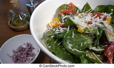 Parmesan cheese falling on a spinach salad with bell pepper and tomatoes, slow motion at 250 fps