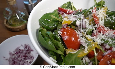 Parmesan cheese falling on a spinach salad with bell pepper...