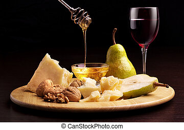 Parmesan cheese, pears, honey, walnuts and wineglass
