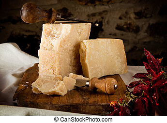 Parmesan cheese with knife on old wooden chopping board, landscape orientation.