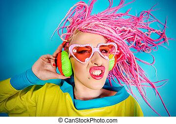 Crazy expressive trendy DJ girl in bright clothes, headphones and bright dreadlocks. Disco, party. Bright fashion.