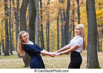 parque, niñas, joven, dos, otoño, manos de valor en cartera