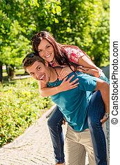 parque, par, ensolarado, abraçando, piggyback, feliz