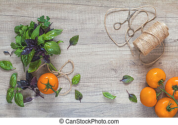 Parsley and basil bunch of bouquets, branch yellow tomatoes, scissors and rope cord on light wooden surface.