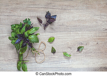 Parsley and basil bunch of bouquets on light wooden surface....