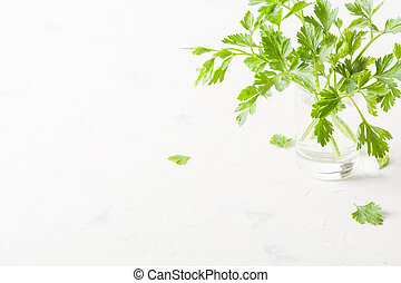 Parsley in a glass with water on a white background.