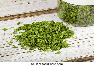 Parsley - pile of dried parsley flakes with container in the...