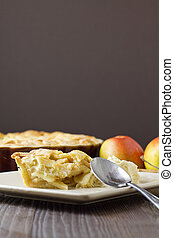 Slice of freshly made apple pie, a la mode, with pastry lattice top on flat plate with apples, cinnamon sticks and the rest of the pie out of focus behind. A spoon rests on the plate, someone having just taken eaten a bite or two. Part of a series of images showing the preparation of traditional ...