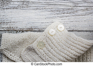 Part knitting on white wooden background with copyspace