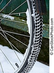 part of a bicycle wheel in the snow near the wall