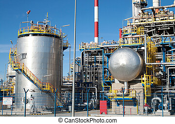 Part of a big oil refinery with many silver pipes and ...