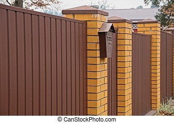 part of a brown fence with a mail box on the street