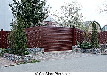 part of a brown wooden fence and closed gates with decorative coniferous trees on the street