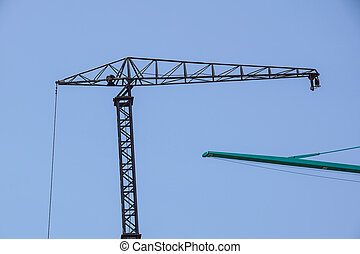 Part of a construction tower crane against the blue sky