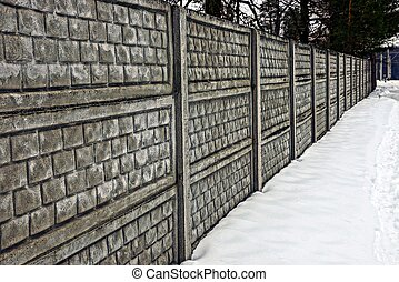 part of a gray concrete fence outdoors in the snow