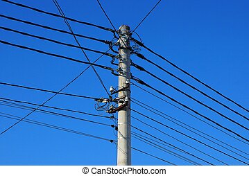 part of a gray concrete pillar with black wires against a blue sky
