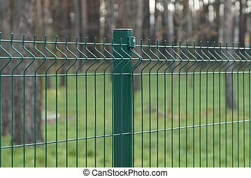 part of a green metal fence made of iron mesh on the street