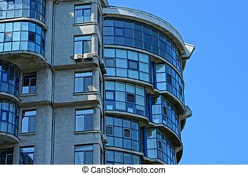 part of a high gray house with windows and balconies against the blue sky
