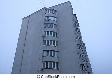 part of a large gray house with balconies and windows against the sky