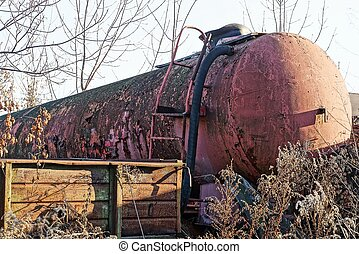 part of a large old cistern rusty and red outside in the dry grass