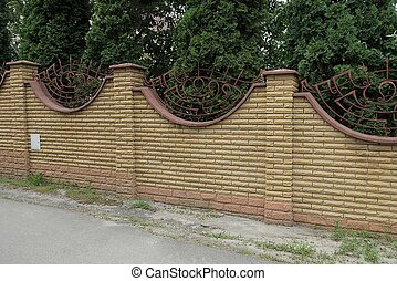 part of a long brick brown fence wall on a gray stone foundation in green grass
