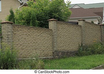 part of a long brick brown fence wall on a gray stone foundation