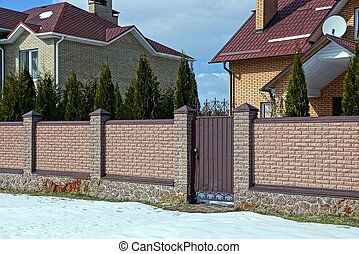 part of a long brown brick fence and a closed door at the road in the snow