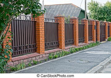 Part of a private iron brown fence and gate at the green grass in the street