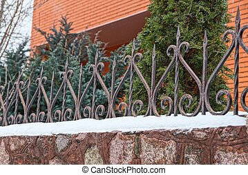 part of a stone fence with gray iron sharp rods in the snow