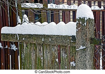 part of a wooden gray fence under the snow