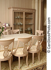 Part of an interior of a dining room in light tones