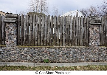 part of an old rural fence made of stones and gray sharp logs outside in the grass