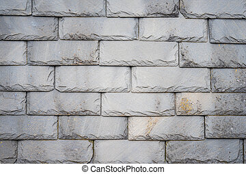 Part of an olf weathered slate tile roof as a background. Closeup detail pattern of grey stone tiles