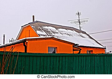 part of an orange house in the snow behind a green fence