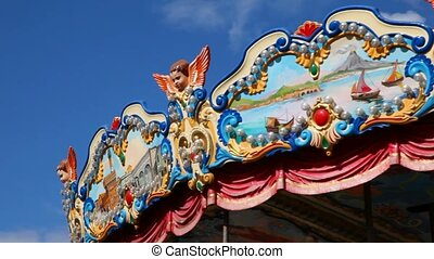 part of carousel merry-go-round amusement rotating on blue sky in city park