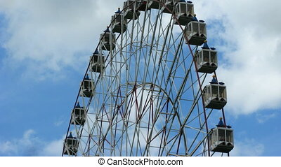 Part of ferris wheel on cloudy sky