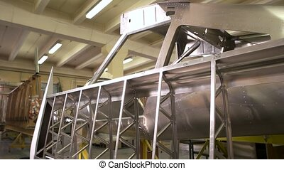 Part of fuselage. Shiny steel in workshop. Materials used in aircraft.