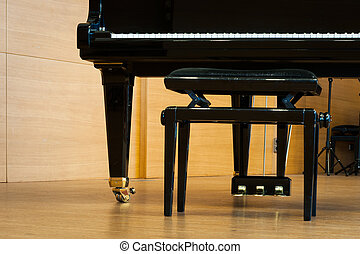 part of grand piano with music stool at wooden floor