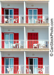 Part of luxury hotel with red shutters.