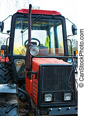 Part of red tractor on the street.