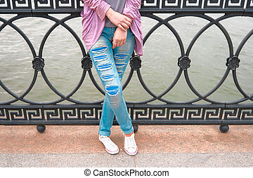 Part of the body  portrait of a casual woman standing with arms folded and legs crossed leaning back metal fence of river embankment