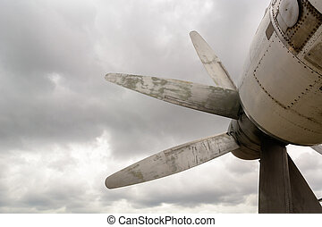 Part of the fuselage of the old military plane with the propeller closeup against the background of an empty and gray sky.