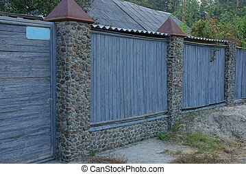 part of the gray fence of wooden boards and stones on the street