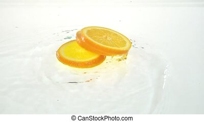Part of the orange drops into the water . White background. Slow motion
