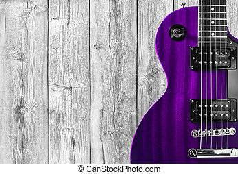 Part of the pink electric guitar on wooden background. A...