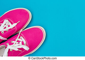 Part of the Pink sneakers with white laces on a blue